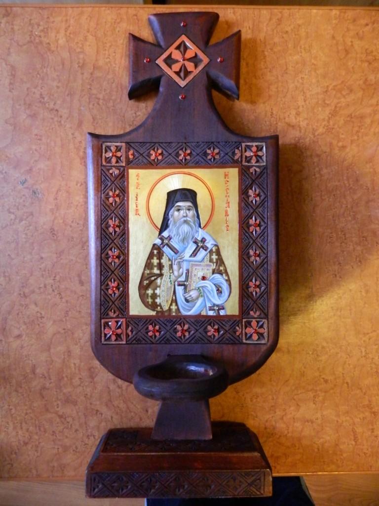 Candela Sf. Ier. Nectarie- Realizata din lemn de tei sculptat, icoana realizata in tehnica bizantina, cu foita de aur de 22k, si aplicatii de pietre semipretioase. Dimensiuni candela 40x25cm, dimensiune icoana 13x11cm