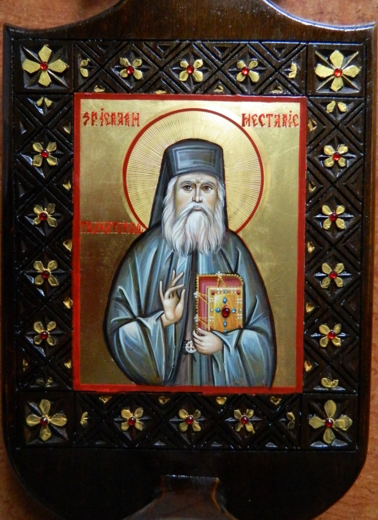 Candela Sfantului Ierarh Nectarie, sculptata manual si pictata in stil bizantin, cu foita de aur de 22k, si aplicatii de pietre semipretioase. Dimensiuni candela 42X20cm, dimensiune icoana 13X11 cm Detaliu